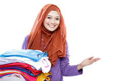 Young woman wearing hijab carrying folded clean clothes while pr Royalty Free Stock Photos