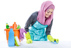 Young woman wearing hijab cleaning white table using sponge Royalty Free Stock Images