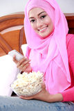 Young woman wearing hijab holding a mobilephone and a bowl of po. Portrait of young woman wearing hijab holding a mobilephone and a bowl of popcorn on bed Stock Photos