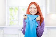Young woman wearing hijab holding and smelling the fresh clean l. Portrait of young woman wearing hijab holding and smelling the fresh clean laundry stock photography