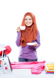 Young woman wearing hijab ironing clothes while enjoying a cup o Stock Image
