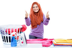 Young woman wearing hijab ironing clothes and giving two thumbs Royalty Free Stock Photography