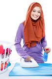 Young woman wearing hijab ironing clothes and spraying perfume Royalty Free Stock Images