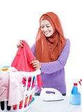 Young woman wearing hijab ironing while pick up a clothes Stock Photography