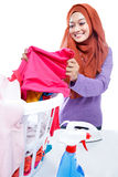 Young woman wearing hijab ironing while pick up a clothes Royalty Free Stock Image