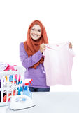 Young woman wearing hijab ironing while pick up a clothes Royalty Free Stock Photo