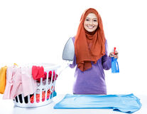 Young woman wearing hijab jolding iron and perfume spray Royalty Free Stock Image
