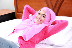 Young woman wearing hijab lying on bed Royalty Free Stock Photography
