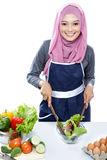 Young woman wearing hijab while making salad. Portrait of young woman wearing hijab while making salad isolated on white Stock Photography