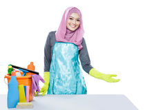 Young woman wearing hijab presenting clean table with cleaning e Stock Image