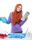 Young woman wearing hijab reading article on tablet while doing Stock Photography