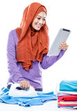 Young woman wearing hijab reading article on tablet while ironin Royalty Free Stock Photos