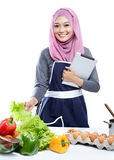 Young  woman wearing hijab reading cooking recipe on tablet whil Royalty Free Stock Images