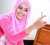 Young woman wearing hijab taking selfie photo. Portrait of young woman wearing pink hijab taking selfie photo with mobilephone Stock Photography