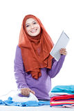 Young woman wearing hijab using tablet while ironing clothes Royalty Free Stock Image