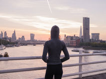 Young woman wearing hoodie on bridge in London at sunrise Royalty Free Stock Photography