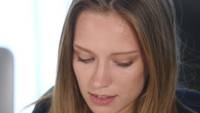 A young woman wearing a jacket in her office. Close up stock footage
