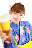 Young woman wearing Japanese kimono with a glass of beer. Concept shot of Japanese woman's lifestyle Stock Photography