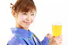 Young woman wearing Japanese kimono with a glass of beer. Concept shot of Japanese woman's lifestyle Royalty Free Stock Photo