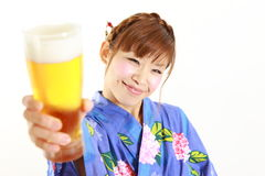Young woman wearing Japanese kimono with a glass of beer Stock Photo