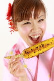 Young woman wearing Japanese kimono with grilled corn. Concept shot of Japanese womans lifestyle Royalty Free Stock Photography
