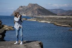 Young woman photographing rock ribbed Koru beach in Gazipasha Al. Young woman wearing jeans gray jacket and backpack standing and photographing rock ribbed beach Stock Photos