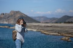 Young woman photographing rock ribbed Koru beach in Gazipasha. Young woman wearing jeans gray jacket and backpack standing and photographing rock ribbed beach in Royalty Free Stock Photography