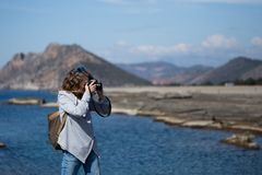 Young woman photographing rock ribbed Koru beach in Gazipasha. Young woman wearing jeans gray jacket and backpack standing and photographing rock ribbed beach in Stock Image