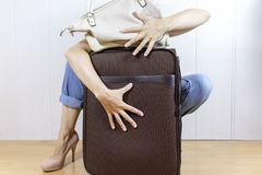 Young woman wearing jeans and high heels cuddles, hugs luggage bags. royalty free stock images