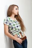 Young woman wearing jeans near wall Royalty Free Stock Photos