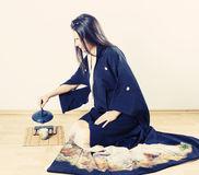 Young woman wearing kimono pouring tea Stock Photos