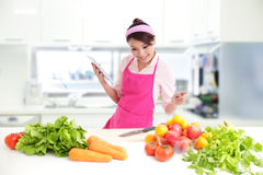 Young woman wearing kitchen apron with tablet royalty free stock photography