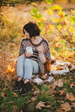 Young woman wearing knitted poncho having picnic in a forest: drinking tea and picking apples Royalty Free Stock Photo