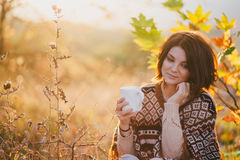 Young woman wearing knitted poncho having picnic in a forest: drinking tea and picking apples Stock Images