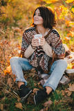 Young woman wearing knitted poncho having picnic in a forest: drinking tea and picking apples Stock Photo