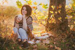Young woman wearing knitted poncho having picnic in a forest: drinking tea and picking apples Royalty Free Stock Image
