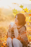 Young woman wearing knitted poncho having picnic in a forest: drinking tea and picking apples Royalty Free Stock Photography