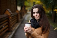 Young woman wearing knitted sweater walking in the autumn park a stock image