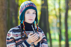 Young woman wearing knitted woolly hat and holding hot yerba mate drink Royalty Free Stock Photography