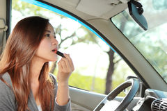 Young woman wearing lipstick in the car Royalty Free Stock Photo