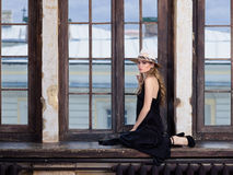 Young woman wearing long black dress and hat Royalty Free Stock Image