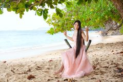 Young woman wearing long pink dress on Hawaiian beach Stock Images