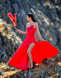 Young woman wearing long red dress and mask Stock Images
