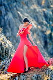 Young woman wearing long red dress and mask Royalty Free Stock Photos