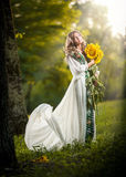 Young woman wearing a long white dress holding sunflowers outdoor shot. Portrait of beautiful blonde girl with yellow flowers Royalty Free Stock Images