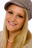 Young woman wearing mod cap smiles at camera Royalty Free Stock Photography