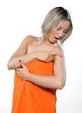 Young woman wearing orange towel checking her mole. Scared young woman wearing orange towel checking her mole Royalty Free Stock Image