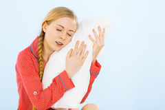 Young woman wearing pajamas hugging soft pillow Royalty Free Stock Photography