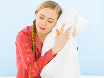 Young woman wearing pajamas hugging soft pillow Stock Photography