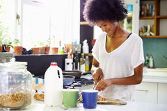 Young Woman Wearing Pajamas Preparing Breakfast In Kitchen Stock Images